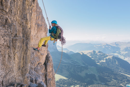 Female rock climber hanging on safety rope