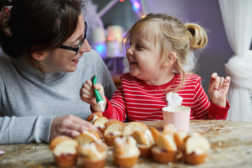 Woman and child making cupcakes together