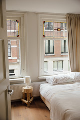 Cozy white bedroom in an apartment overlooking another old apartment in Amsterdam