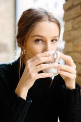 Dreaming young woman enjoying coffee