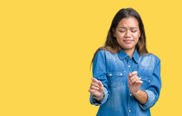 Young beautiful brunette woman wearing blue denim shirt over isolated background disgusted expression, displeased and fearful doing disgust face because aversion reaction. With hands raised