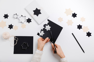 Female hands cut star-shaped cards to make gift package