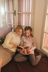 Mother And Daughter Sitting On Bed And Reading A Book