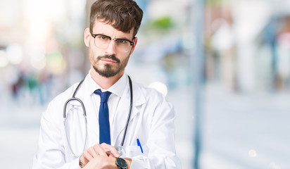 Young doctor man wearing hospital coat over isolated background In hurry pointing to watch time, impatience, upset and angry for deadline delay