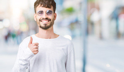 Young handsome man wearing sunglasses over isolated background doing happy thumbs up gesture with hand. Approving expression looking at the camera with showing success.