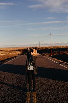 Female Photographer Taking Photographs on Desert Road at Sunrise