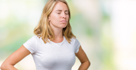 Beautiful young woman wearing casual white t-shirt over isolated background with hand on stomach because indigestion, painful illness feeling unwell. Ache concept.