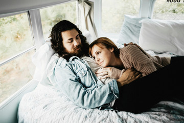 Cute hipster couple cuddling in converted school bus tiny home