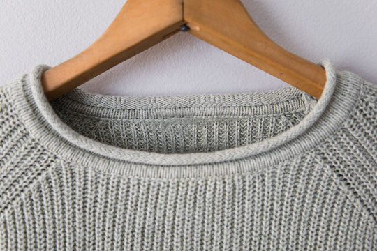 Light green sweater hanging on grey wall