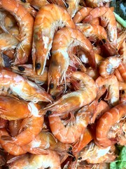 Large orange fresh shrimps on the storefront in the store. Cropped shot, close-up, a lot, top view. The concept of nutrition and health.