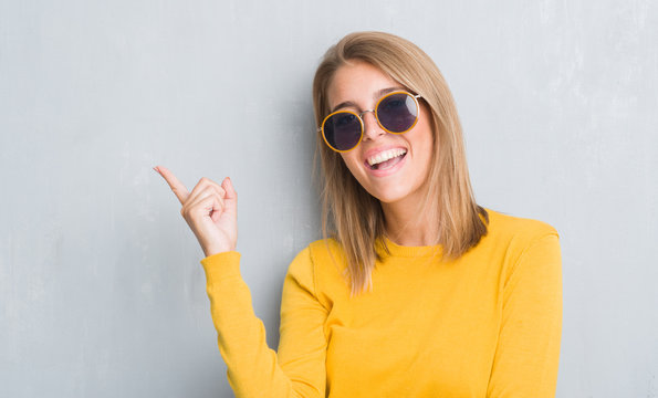 Beautiful young woman standing over grunge grey wall wearing retro sunglasses very happy pointing with hand and finger to the side