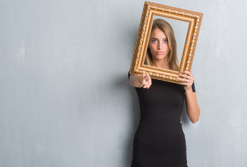 Beautiful young woman over grunge grey wall holding vintage frame pointing with finger to the camera and to you, hand sign, positive and confident gesture from the front