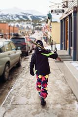 Child walking through ski town with skis on shoulder