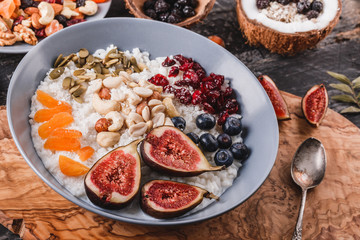 Rice coconut porridge with figs, berries, nuts, dried apricots and coconut milk in plate on rustic wooden background. Healthy breakfast ingredients. Clean eating, vegan food concept. Top view