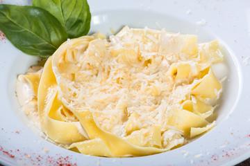 Fettuccine pasta with parmesan cheese, basil and cream sauce on dark wooden background, Italian cuisine. Ingredients on table