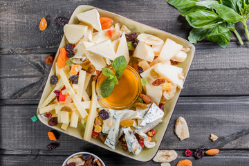 Cheese platter garnished with pear, honey, walnuts on plate on wooden background. Snacks and Wine appetizers set. Top view