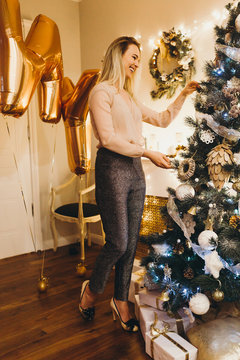 A woman decorating a Christmas tree wearing festive outfit