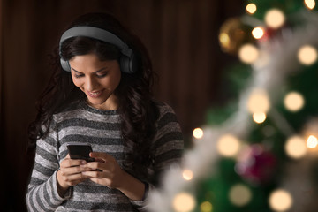 Woman using mobile phone while listening to music during Christmas