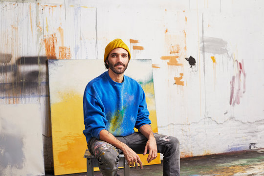 Confident Artist Sitting Against Painting In Studio