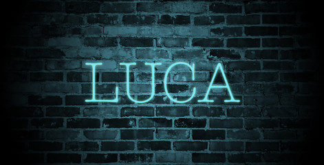 first name Luca in blue neon on brick wall