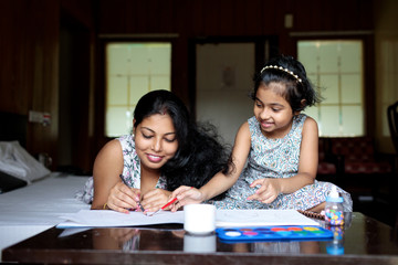 Little girl sharing cheerful moment with her mother while painting together