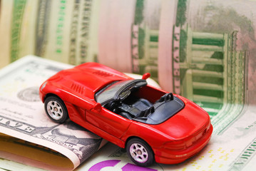 Toy sports car on the background of banknotes.