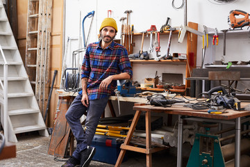 Confident Man Leaning On Workbench In Workshop