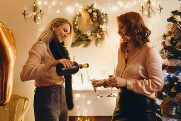 two girls celebrating New Year drinking champagne