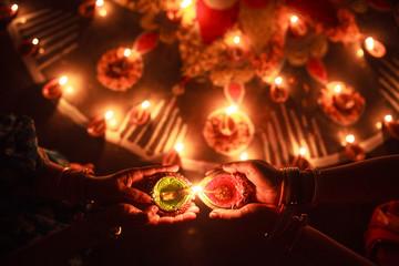 Woman enlightening Diya in Rangoli at Diwali Celebration