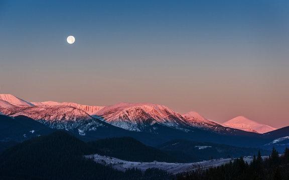 Full moon above the sunrise snow mountain peaks