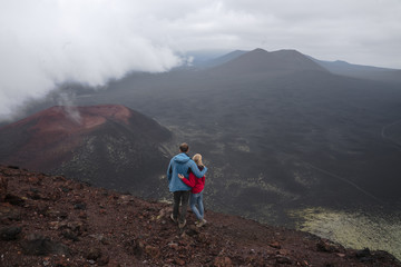 Two lonely unrecognized anonymous persons stands with beautiful view on volcano with backpack