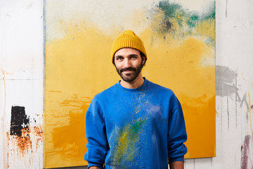 Smiling Male Painter Against Painting In Studio