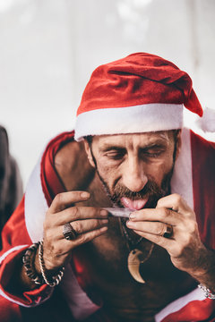 Bad Santa rolling a cigarette with weed