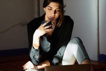 Content woman enjoying coffeeat laptop