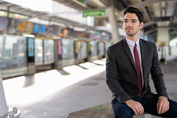Portrait of young handsome businessman sitting at train station