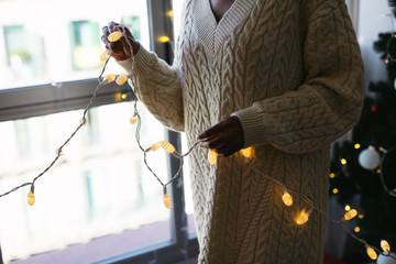 Closeup of a woman holding Christmas lights at home.