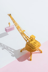 Yellow crane with pink container.