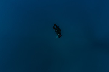 Man swimming above blue depth of sea