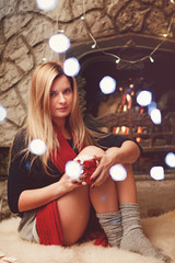 Pretty blonde woman near fireplace with cup of coffee with marshmallow