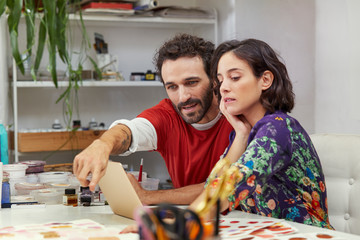 Artist Pointing At Illustration While Using Laptop With Woman