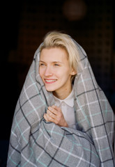Portrait of young woman wrapped in a blanket slightly out-of-focus