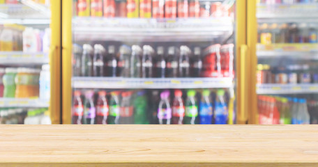 wood table top with supermarket convenience store refrigerators with soft drink bottles on shelves abstract blur background