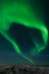 Northern lights, aurora in the night sky above the snowy hills.