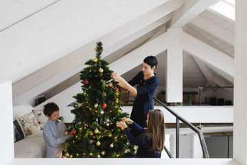 Mother and children decorating the Christmas tree together