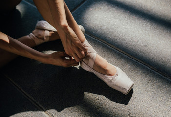 Crop ballerina tying pointe shoes