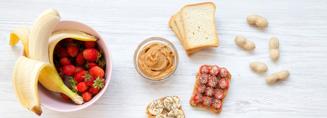 Vegan toasts with fruits, seeds, peanut butter. White wooden background, top view. From above. Flat lay.