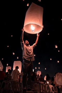 Chiang Mai Thailand white lantern to release in the sky during Loi Krathong Yee Peng Festival, young men release lantern in the sky