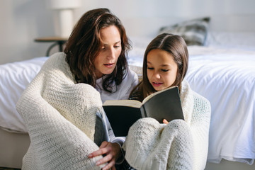 Mom and her daughter reading a book on bedroom in the morning.