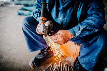 close up industrial workers hands cutting iron with angle grinder