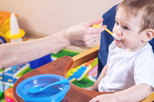113a76fb8 Little baby boy eating on a chair in the kitchen. Mom feeds holding in hand